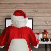 Image of Santa's back sitting at computer for Christmas planning