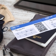 Image of airplane boarding pass on top of passport and money wallet on table