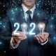 Man holding 2 with a lightblub to stand for the 0 in 2020