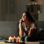 Woman sitting on phone after power outage utilities scam