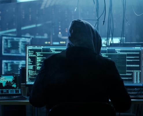 Image of hacker at computer pulling off international fraud scheme